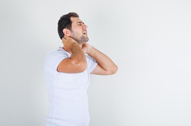 Молодой человек в белой футболке страдает от боли в шее и выглядит болезненно