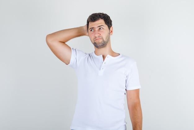 頭の後ろに手で白いtシャツ思考の若い男