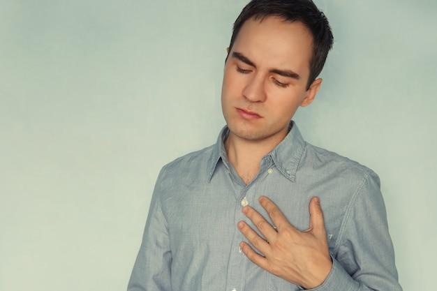 強い心臓発作、精神的な痛み、精神的な苦しみを持つ白いtシャツの若い男。経験、感情、感情、心配、
