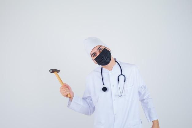白い制服を着た若い男、手にハンマーを保持し、怒っているように見えるマスク、正面図。
