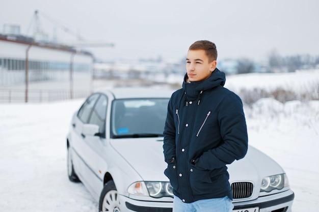 겨울 옷 차 근처에 서있는 젊은 남자