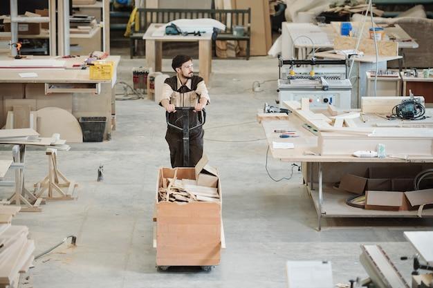 Молодой человек в спецодежде и очках, опираясь на ручку тележки с остатками еды, несет их в цех обработки