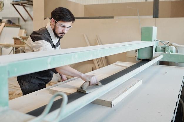 Молодой человек в спецодежде наклоняется над верстаком и гладит поверхность заготовки деревянным ручным инструментом во время работы на заводе