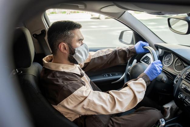 オンラインショップやスーパーマーケットから注文を配達するためにクライアントに運転しながら作業服、マスク、手袋を着用した若い男