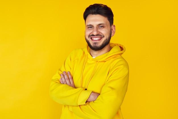 Молодой человек в желтой толстовке с капюшоном улыбается со скрещенными руками