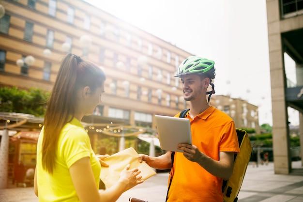 노란색 셔츠를 입은 청년은 도시 거리에서 주문을 추적하기 위해 가제트를 사용하여 소포를 배달합니다. 온라인 앱을 사용하여 지불, 주소 및 수령인을 만나는 택배. 현대 기술.