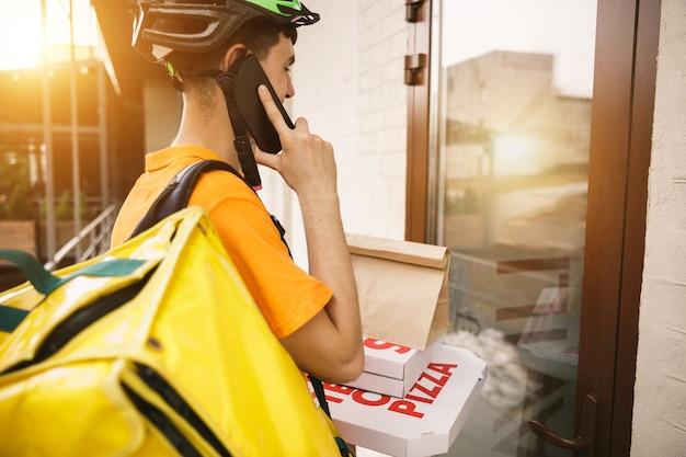 노란색 셔츠를 입은 청년이 도시 거리에서 주문을 추적하기 위해 가제트를 사용하여 피자를 배달합니다. 지불을 받고 배송 주소를 추적하기 위해 온라인 앱을 사용하는 택배. 현대 기술.