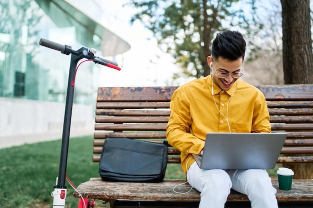 ノートパソコンとスクーターと公園で勉強している黄色いシャツの若い男