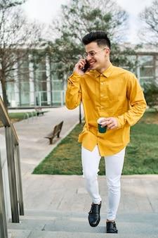전화로 얘기하고 커피를 마시는 노란색 셔츠에 젊은 남자