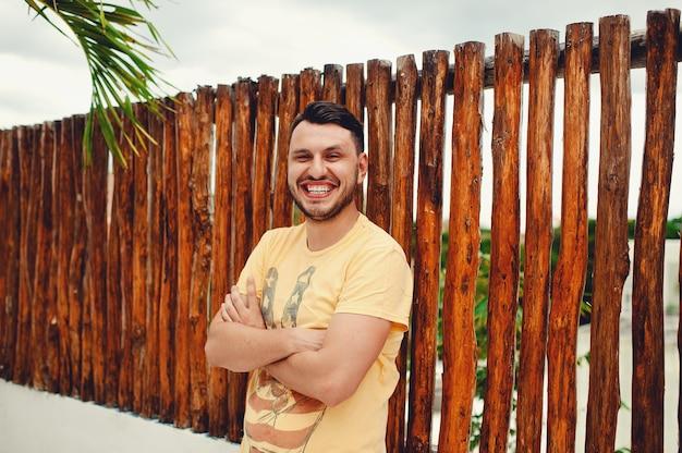 Молодой человек в желтой футболке со скрещенными руками улыбается у деревянного забора