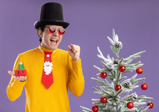 黄色のタートルネックと黒い帽子と面白いネクタイを身に着けている若い男は、紫色の背景の上のクリスマスツリーの横に興奮して幸せに立って新年の日付とキューブを保持しています