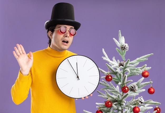 紫色の背景の上のクリスマスツリーの横に立って腕を上げて混乱しているカメラを見て壁時計を保持している黒い帽子をかぶった黄色のタートルネックと眼鏡の若い男