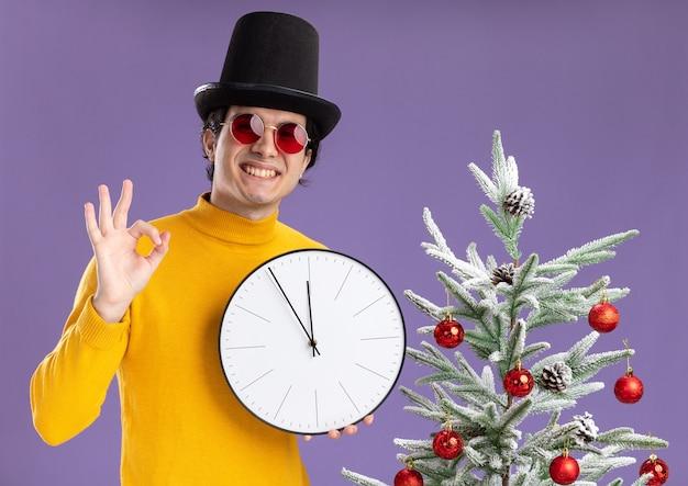노란색 터틀넥과 보라색 배경 위에 크리스마스 트리 옆에 서있는 확인 표시를 보여주는 카메라를보고 웃 고 벽 시계를 들고 검은 모자를 쓰고 안경에 젊은 남자