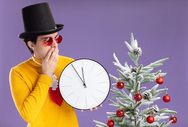 黄色いタートルネックとそれを見て壁時計を保持している黒い帽子をかぶった眼鏡の若い男は、紫色の壁の上のクリスマスツリーの横に立って興味をそそられました