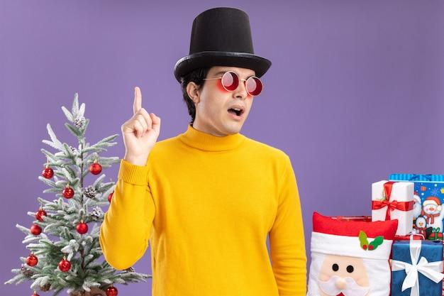 노란색 터틀넥과 검은 모자를 쓰고 안경에 젊은 남자가 제쳐두고 놀란 검지 손가락이 크리스마스 트리 옆에 서서 보라색 벽에 선물합니다.