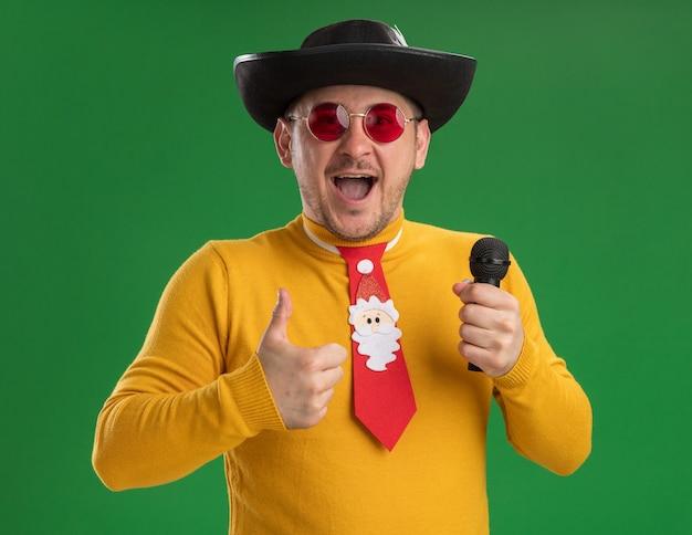 緑の壁の上に立って親指を見せて幸せで興奮しているマイクを保持している面白い赤いネクタイと黄色のタートルネックとメガネの若い男