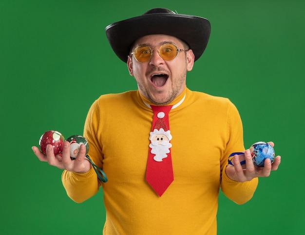 Молодой человек в желтой водолазке и очках с забавным красным галстуком держит игрушки для елки, счастлив и взволнован, стоя у зеленой стены