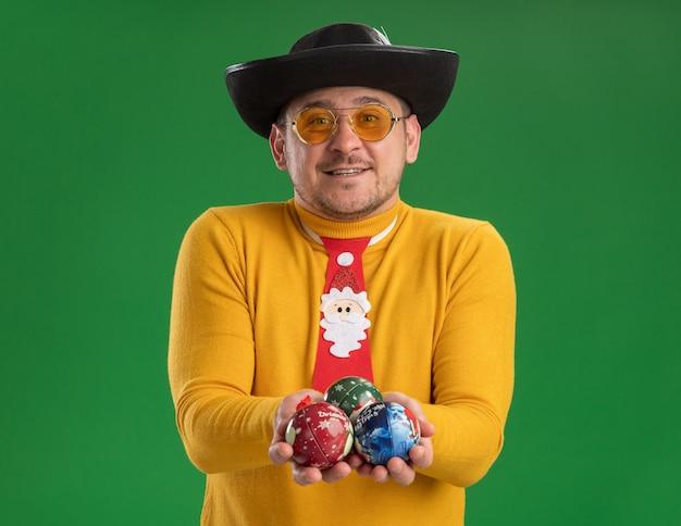 Молодой человек в желтой водолазке и очках с забавным красным галстуком держит игрушки для елки, глядя в камеру, счастливый и веселый улыбается, стоя на зеленом фоне