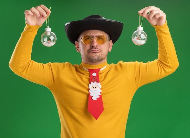 노란색 터틀넥과 녹색 벽 위에 서있는 입술을 추구하는 슬픈 표정으로 크리스마스 트리 장난감을 들고 재미있는 빨간 넥타이와 안경에 젊은 남자