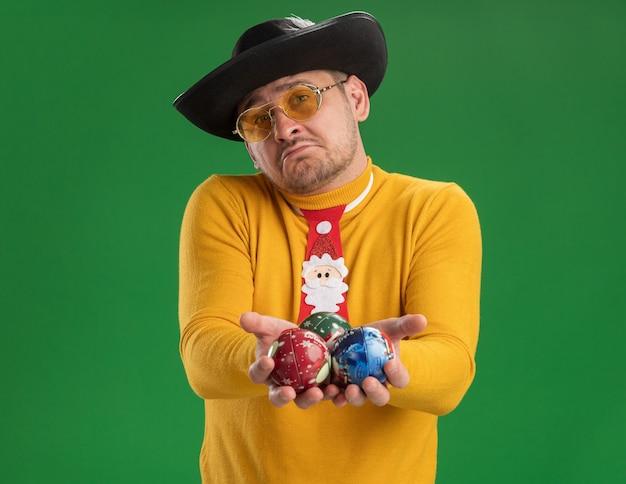Молодой человек в желтой водолазке и очках с забавным красным галстуком держит игрушки для елки с грустным выражением лица, стоящий над зеленой стеной