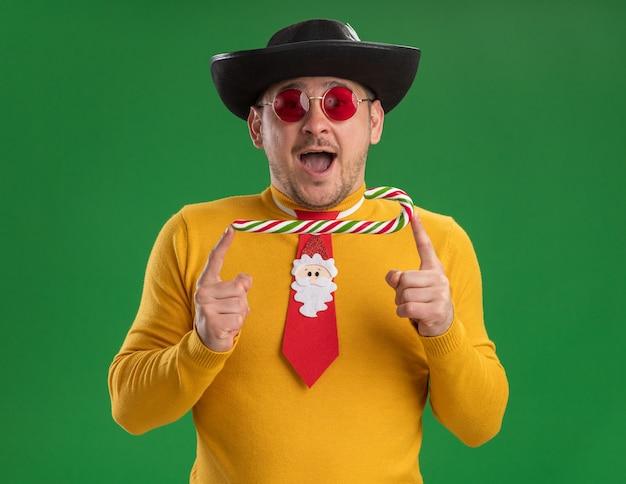 노란색 터틀넥과 녹색 벽 위에 사탕 지팡이를 들고 검은 모자에 재미있는 빨간 넥타이와 안경에 젊은 남자가 행복하고 놀란 서