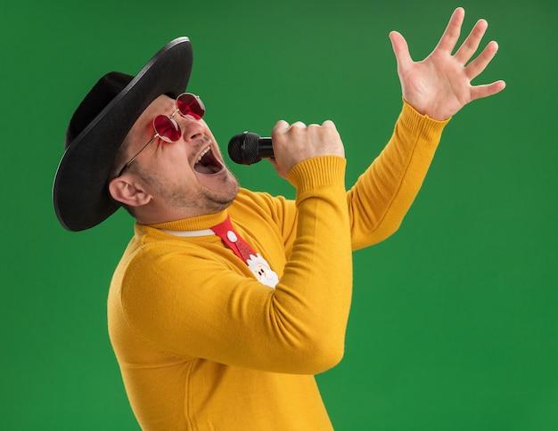 緑の壁の上に立って感情的で興奮してマイクに向かって叫んでいる面白い赤いネクタイと黄色のタートルネックとメガネの若い男