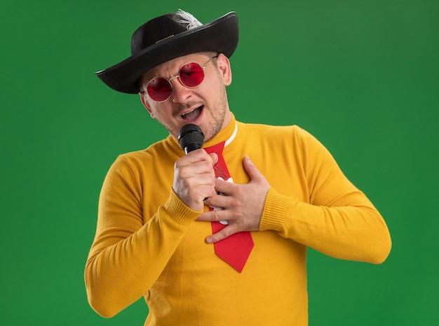 緑の壁の上に立って幸せで楽しいマイクを持って歌っている面白い赤いネクタイと黄色のタートルネックとメガネの若い男