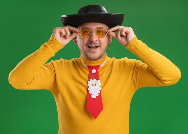 노란색 터틀넥과 녹색 벽 위에 서 웃는 행복한 얼굴로 재미있는 빨간 넥타이와 안경에 젊은 남자
