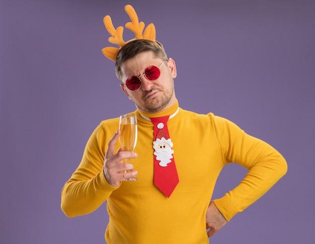 Молодой человек в желтой водолазке и красных очках в забавном красном галстуке и оправе с оленьими рогами держит бокал шампанского и недовольно смотрит на него, стоя на фиолетовом фоне
