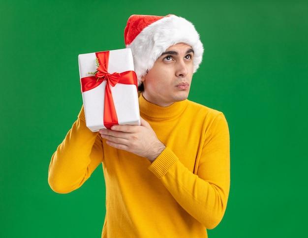 노란색 터틀넥과 산타 모자에 젊은 남자가 녹색 배경 위에 서있는 호기심을 찾고 그의 귀에 선물을 들고