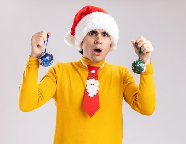크리스마스 공을 들고 노란색 터틀넥과 산타 모자에있는 젊은 남자가 놀랐고 흰 벽 위에 서서 놀랐습니다.
