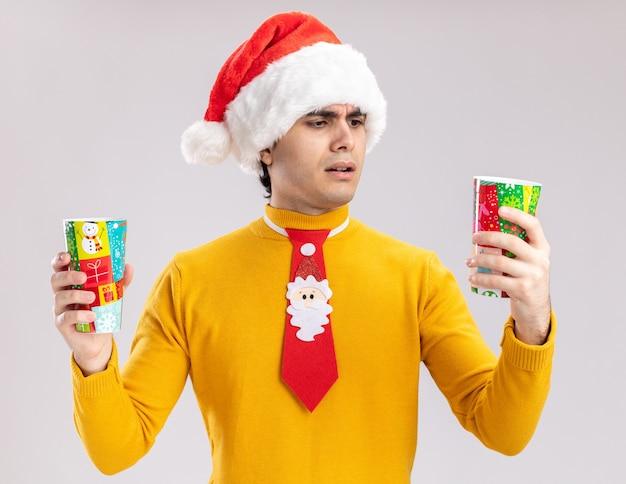 노란색 터틀넥과 흰색 벽 위에 서있는 의심을 갖는 혼란 찾고 다채로운 종이 컵을 들고 재미있는 넥타이와 산타 모자에 젊은 남자
