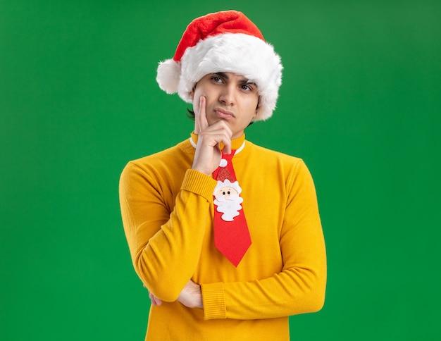 黄色のタートルネックとサンタの帽子をかぶった若い男が緑の背景の上に立って物思いにふける表現を考えてあごに手を脇に見て面白いネクタイ