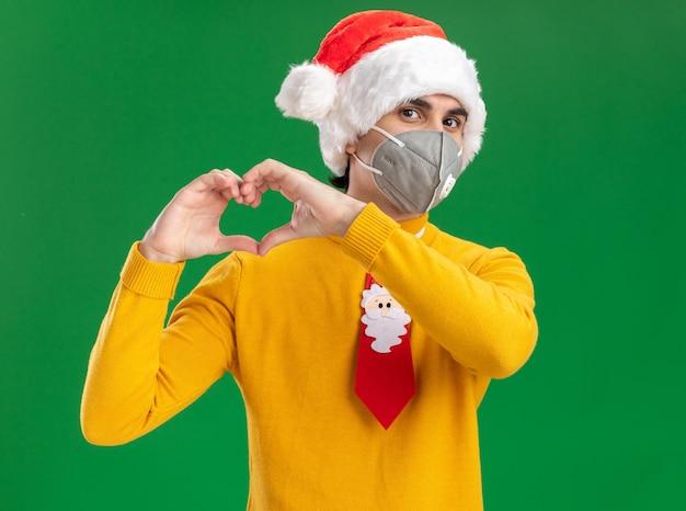 녹색 배경 위에 서있는 손가락으로 심장 제스처를 만드는 얼굴 보호 마스크를 쓰고 재미있는 넥타이로 노란색 터틀넥과 산타 모자에있는 젊은 남자