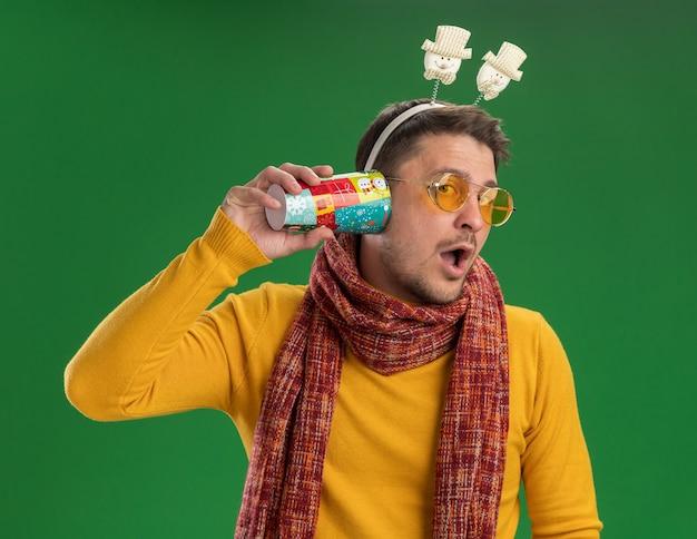 따뜻한 스카프와 녹색 벽 위에 서있는 수군을 듣고 귀에 다채로운 컵을 들고 머리에 재미있는 테두리를 착용하는 안경 노란색 터틀넥에 젊은 남자