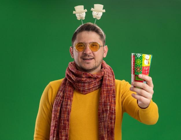 따뜻한 스카프와 녹색 벽 위에 서있는 얼굴에 미소로 다채로운 컵을 들고 머리에 재미있는 테두리를 착용하는 안경 노란색 터틀넥에 젊은 남자