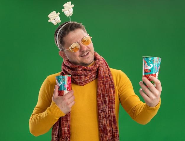 따뜻한 스카프와 녹색 벽 위에 서있는 얼굴에 미소로 그들을보고 다채로운 컵을 들고 머리에 재미있는 테두리를 착용하는 안경 노란색 터틀넥에 젊은 남자