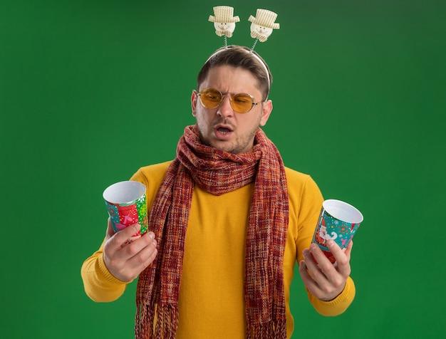 따뜻한 스카프와 녹색 벽 위에 서있는 의심을 갖는 혼란 찾고 두 개의 다채로운 컵을 들고 머리에 재미있는 테두리를 착용하는 안경 노란색 터틀넥에 젊은 남자