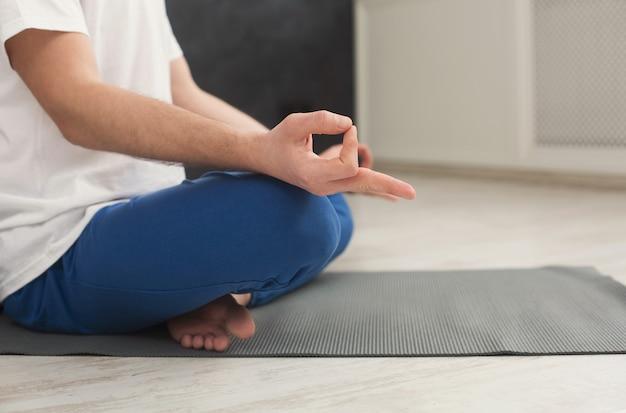 ヨガのクラス、瞑想の練習の若い男。認識できない男はリラックスのために蓮華座をします。フィットネスクラブでの健康的なライフスタイル、コピースペース