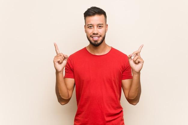 Молодой человек указывает обоими пальцами вверх, показывая пустое пространство.