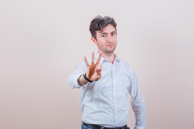 흰색 셔츠, 청바지에 3 번을 나타내는 젊은 남자가 자신감을 찾고