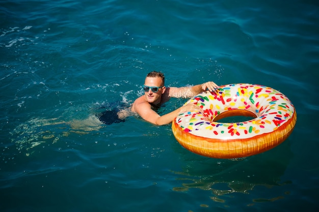 Young man on an inflatable ring in the sea resting and swimming on a sunny day