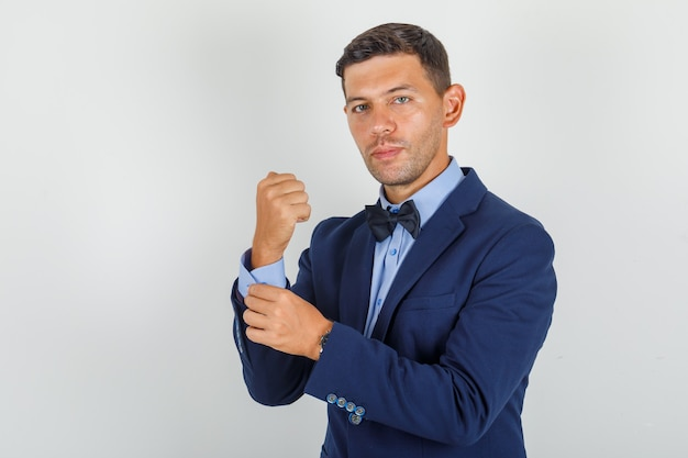若い男がスーツで彼の手首にボタンを挿入し、自信を持って探しています。