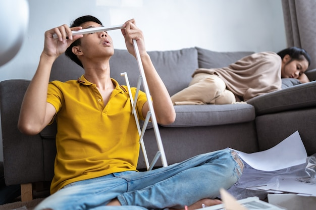 A young man intending to assemble a shelf in the living room at home.
