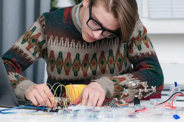 電子部品を熱心に扱っている青年。