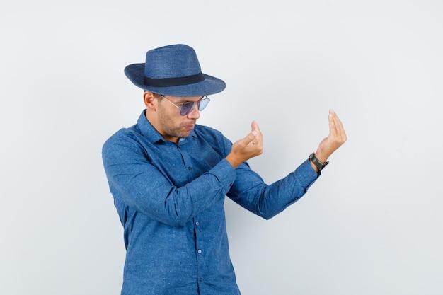 Giovane che invita a venire in camicia blu, cappello e sembra fiducioso. vista frontale.