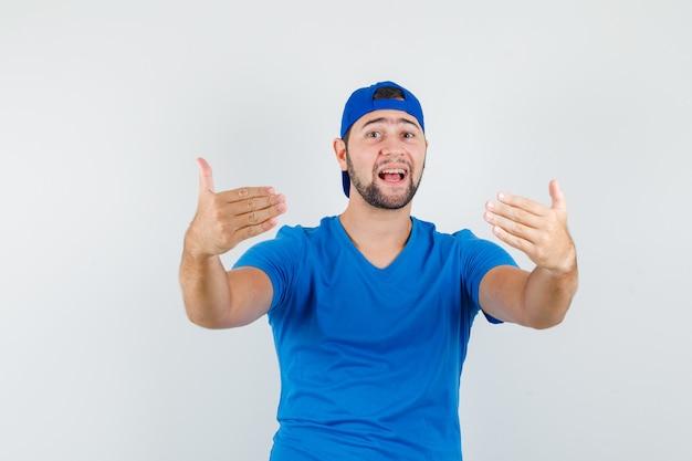 青いtシャツとキャップで来るように誘う若い男