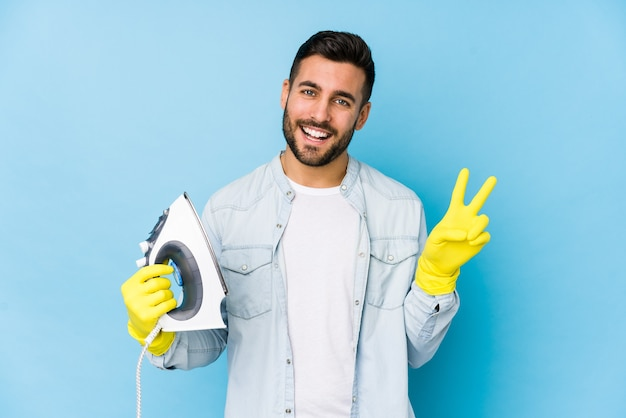 Young man ironing isolated joyful and carefree showing a peace symbol with fingers.