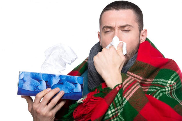 Young man is blowing his nose in a handkerchief.