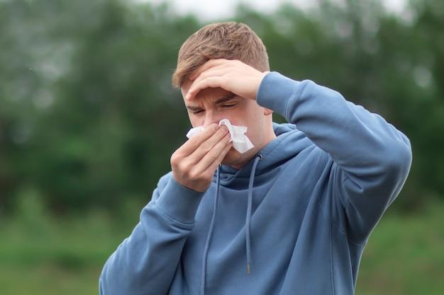 젊은 남자가 두통으로 고통받는 손수건에 코를 불고있다